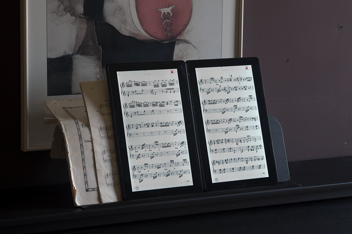 Scora Doble tablets on piano with paper books behind